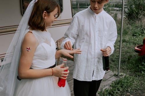 Man in White Dress Shirt Holding Woman in White Dress