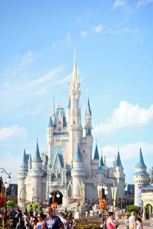 White fairy tale castle with blue roofs in amusement park in Orlando against bright sky on sunny day