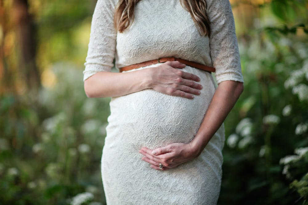 Pregnant woman holding her belly. | Photo: Pexels