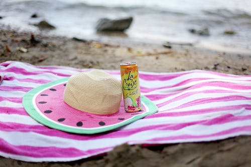 Striped towel spread on sandy beach with straw hat and juice can