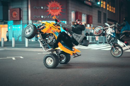 Man in Black Jacket Riding Orange Sports Bike on Road