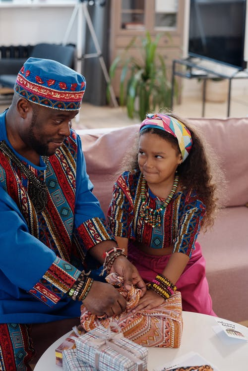 Photo Of Father Helping Daughter To Wrap Gifts