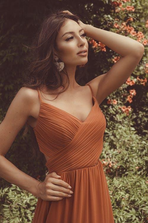 Woman in Orange Spaghetti Strap Dress Standing Near Green Plants