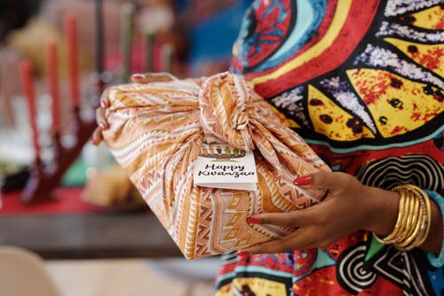 Photo Of Person Holding Gift Wrapped In Cloth