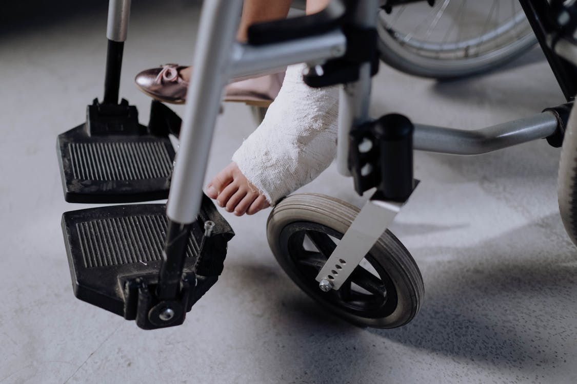 Person in White Pants Riding on Black and Gray Stationary Bike