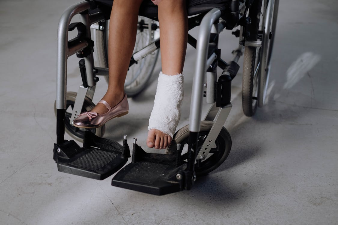 Woman in White Socks Sitting on Black and Gray Exercise Equipment