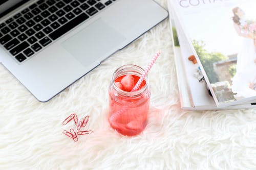 Flat Lay Photo of Glass of Beverage Beside Magazines and Laptop