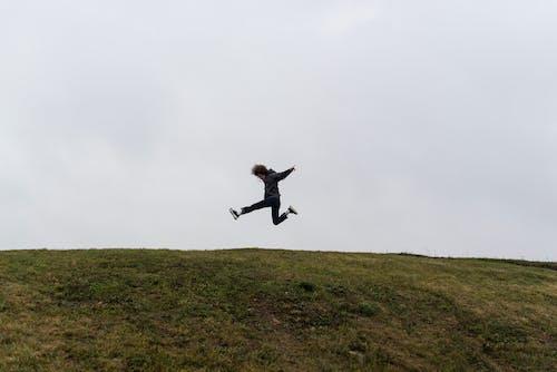 Man in Black Jacket Jumping on Green Grass Field