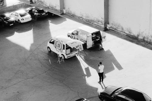 Black and white from above of man standing near coffee truck and car with easel on parking lot with cars