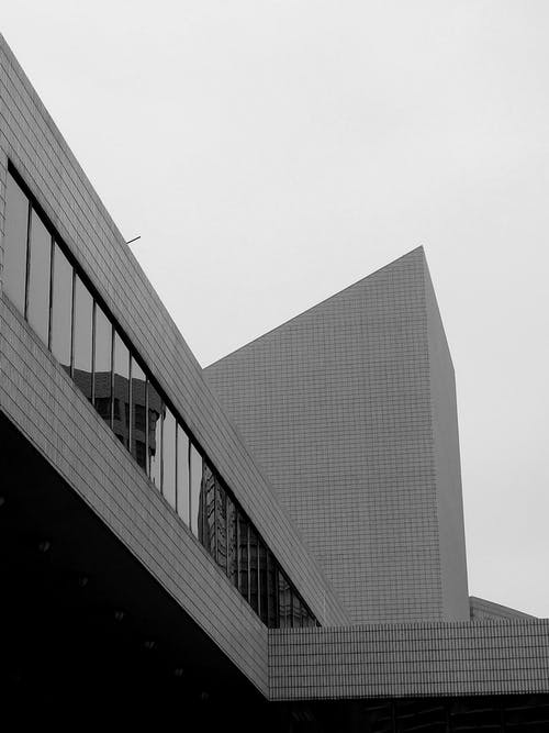 Black and white of contemporary building exterior with glass windows against cloudless sky in city center