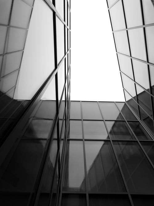 Black and white from below of tall contemporary building exterior with glass windows and walls under bright cloudless sky in daytime
