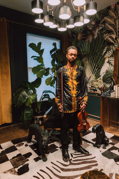 Photo Of A Man Wearing A Dashiki Shirt And Black Pants With Violin