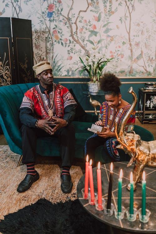 Man in Red Dashiki Shirt Sitting Beside Woman