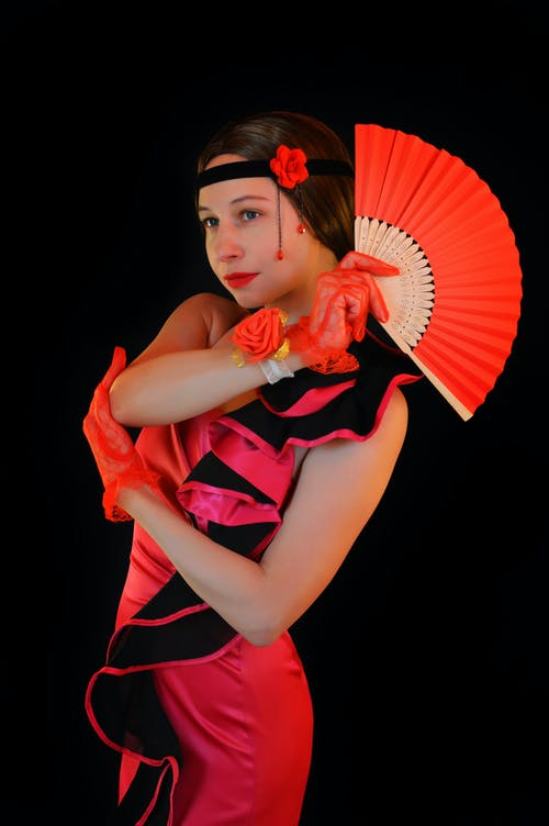 Charming female dancer in bright stylish flamenco costume standing with red fan and looking away against black wall in studio