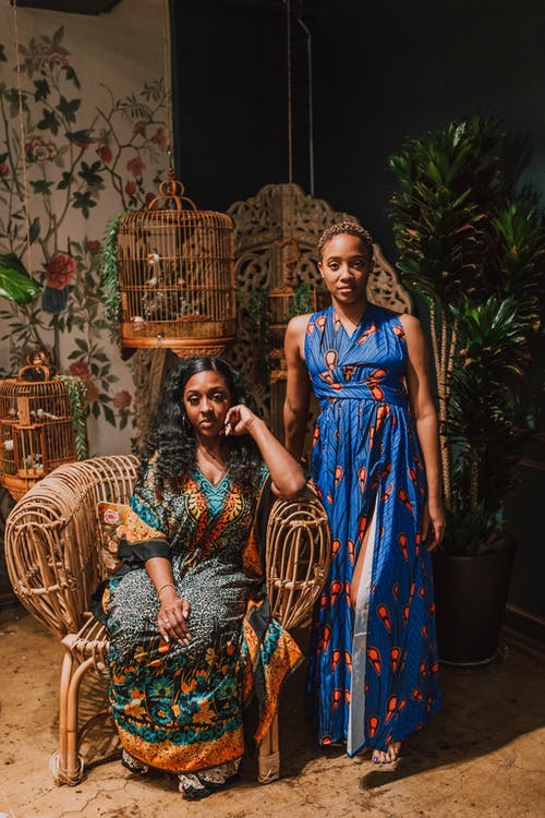 Woman in Green and Brown Floral Dress Standing Beside Woman in Blue and Brown Floral Dress