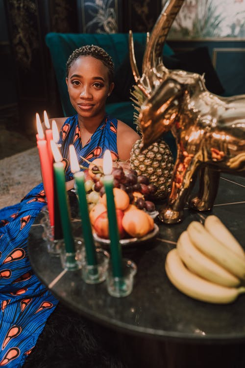 Woman Sitting By The Table With Fruits And Candles