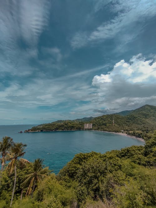 Picturesque scenery of turquoise sea surrounded by green hills covered with exotic plants under cloudy sky