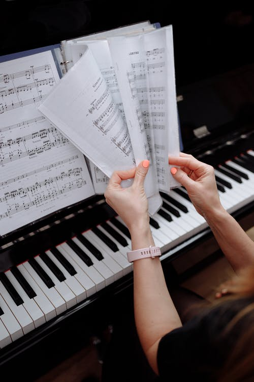 Person Holding Musical Notes on Piano