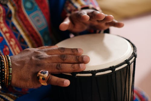 Close-Up Photo Of Person Playing Djembe