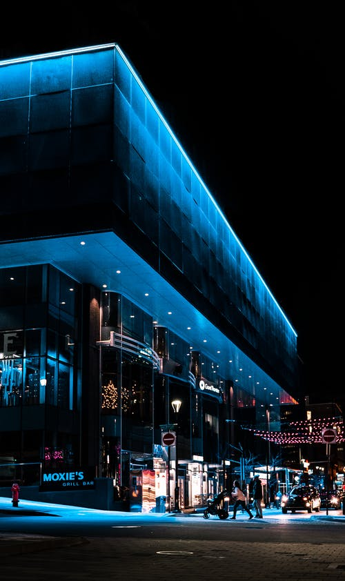 Contemporary urban bar exterior with blue walls against decorative garlands and anonymous people in evening