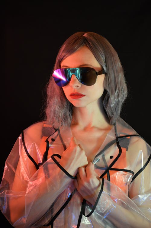 Confident woman with hairstyle and makeup in trendy sunglasses and transparent raincoat standing in studio with black wall