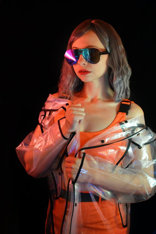 Serious model in trendy sunglasses and raincoat against black wall