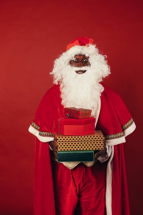 Santa Claus Holding Christmas Presents on Red Background