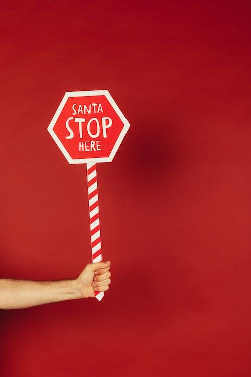 Pessoa Segurando A Placa Vermelha E Branca Do Papai Noel Pare Aqui