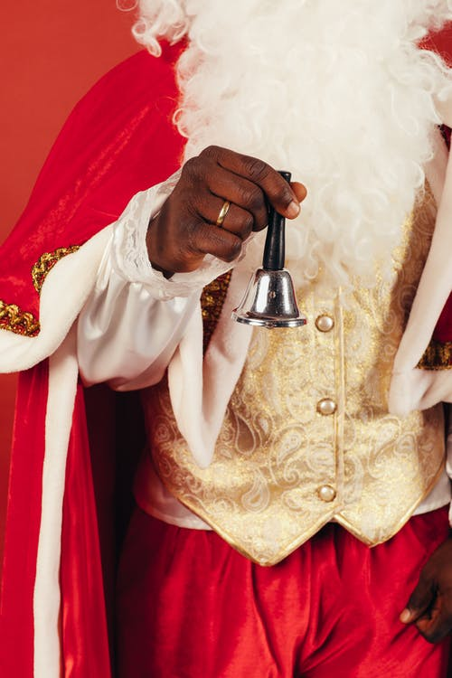 Person Wearing Santa Claus Outfit While Holding a Bell