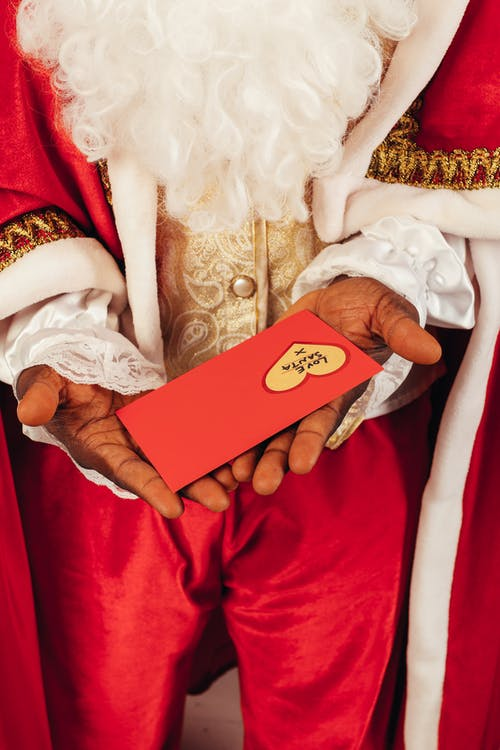 Person Wearing Santa Claus Outfit While Holding Christmas Letter