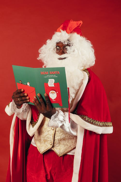 Santa Claus Looking Surprised While Holding Green Book