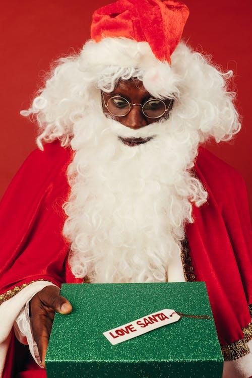 Man in Santa Claus Costume Looking Surprised at Christmas Present