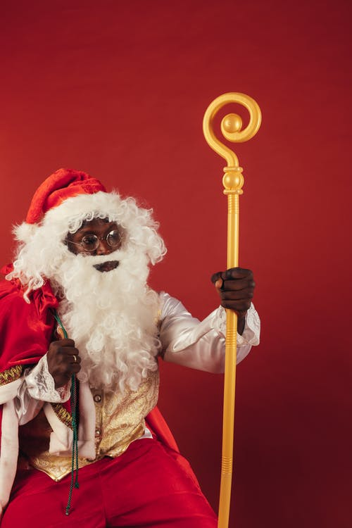 Santa Claus Holding Yellow Stick on Red Background