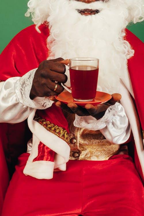 Pessoa Com Roupa De Papai Noel Segurando Uma Xícara De Chá