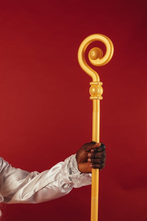 Person Holding a Yellow Staff on Red Background