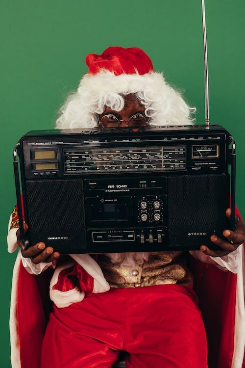 Hombre En Traje De Santa Sosteniendo Una Radio Clásica Negra
