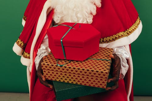 Person In Santa Claus Outfit Holding Gifts