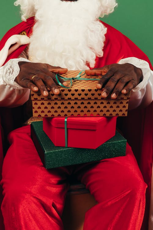 Person Wearing A Santa Outfit With Gifts On His Lap