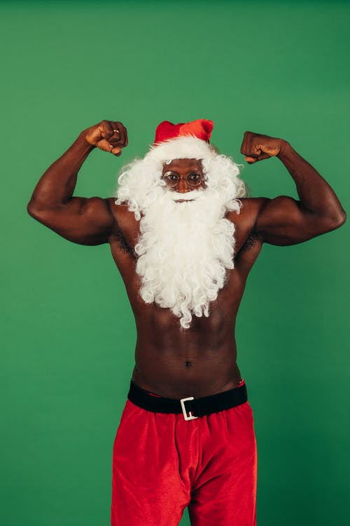 Shirtless Man In Santa Outfit Flexing His Muscles