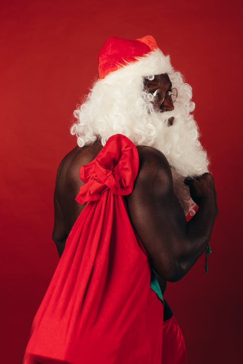 Shirtless Man In A Santa Outfit Carrying Gifts