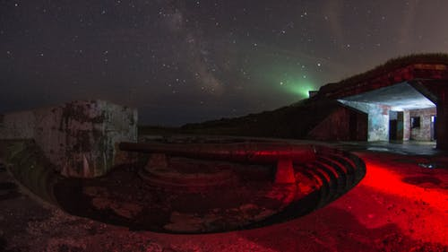 Concrete reservoir with metal pipe at night