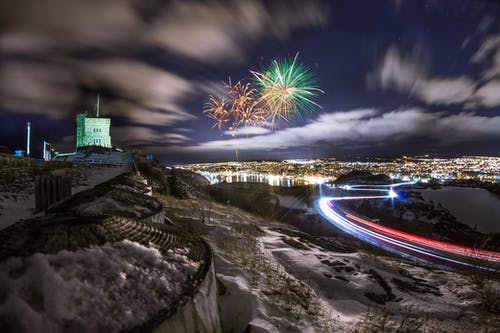 Bright multicolored fireworks exploding in dark sky under city with luminous lights at night