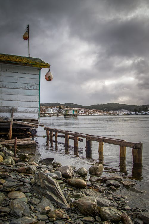 Aged construction on shore with fence and stones against ocean and mounts under cloudy sky