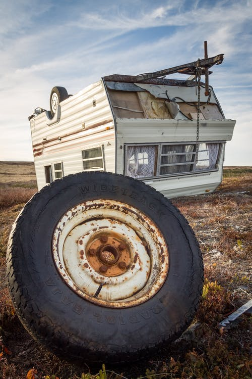 Caravan and rusty wheel after accident on land in countryside