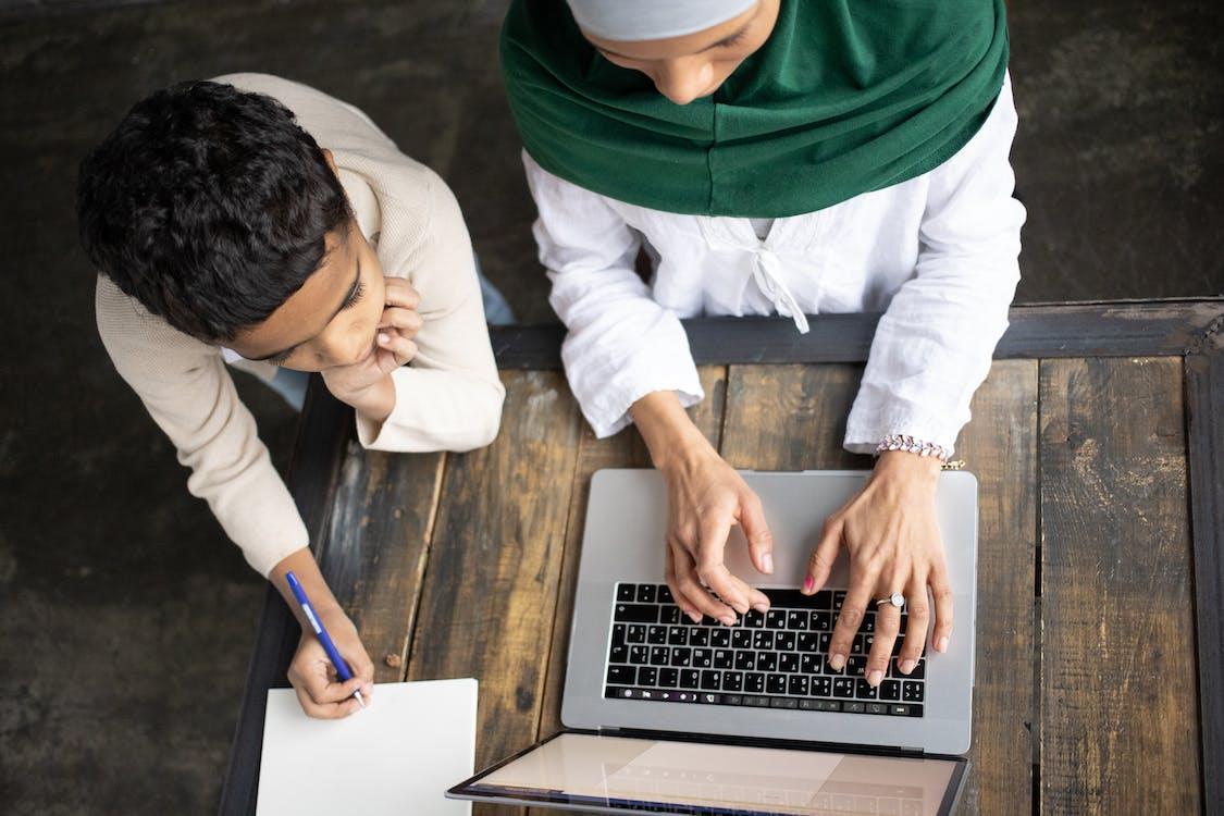 Persona En Sudadera Con Capucha Verde Con Macbook Pro