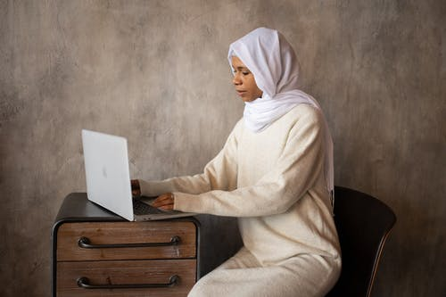 Side view of ethnic female in headscarf typing on netbook placed on wooden cabinet