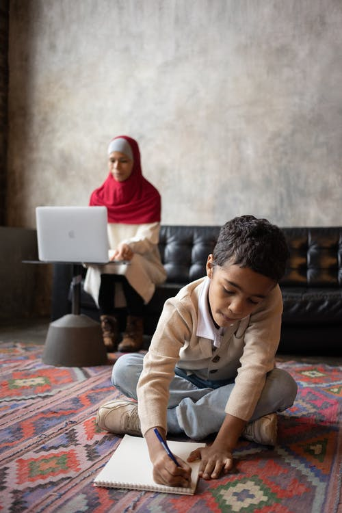 Arabian son writing in notebook near mother working with laptop