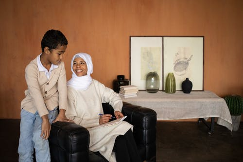 Arabian Muslim mother with son near table with glassware