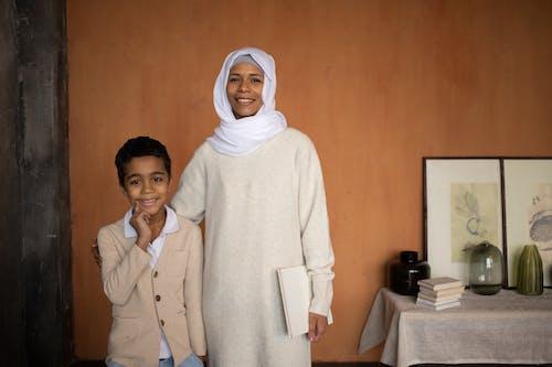 Muslim Arabian cheerful mother in hijab with happy son