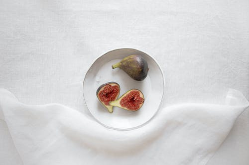 Fresh healthy figs placed on white plate